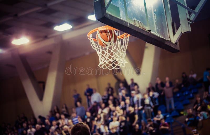 Das Gewinnen zählend, zeigt auf ein Basketballspiel stockbild