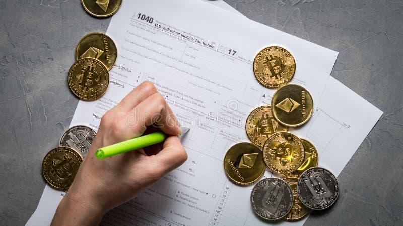 Das girl& x27; s-Hand füllt das Steuerformular für das Zahlen von Steuern vom Bergbau und vom Handel von Schlüssel-währungen lizenzfreie stockbilder