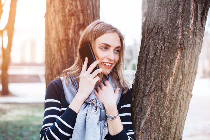 Das glückliche Hippie-Mädchen, das angenehmes Handygespräch mit Freund hat, während ist, Wege parken im Frühjahr, lächelnde Frau  stockbild