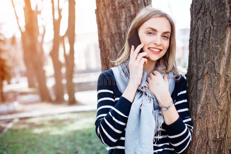 Das glückliche Hippie-Mädchen, das angenehmes Handygespräch mit Freund hat, während ist, Wege parken im Frühjahr, lächelnde Frau  stockfotos