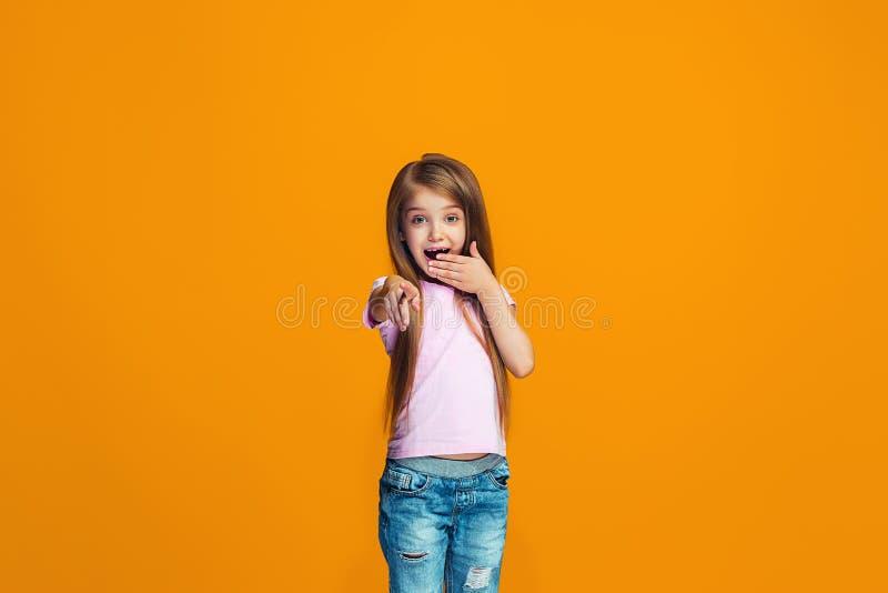 Das glückliche jugendlich Mädchen, das auf Sie, halbes Längennahaufnahmeporträt auf orange Hintergrund zeigt lizenzfreies stockbild
