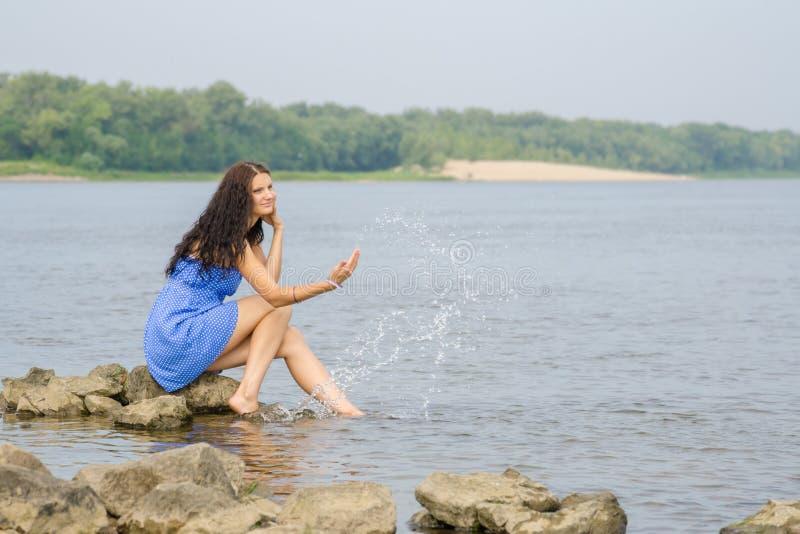 Das glückliche junge Mädchen, das auf der Bank von Fluss Bedingung genießend sitzt, kommt Sommer lizenzfreies stockfoto