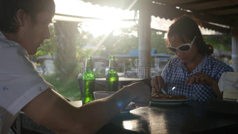 Das glückliche junge Paar, das Mahlzeit isst, trinkt Bier im Freiencafé am Sommertag lizenzfreies stockbild