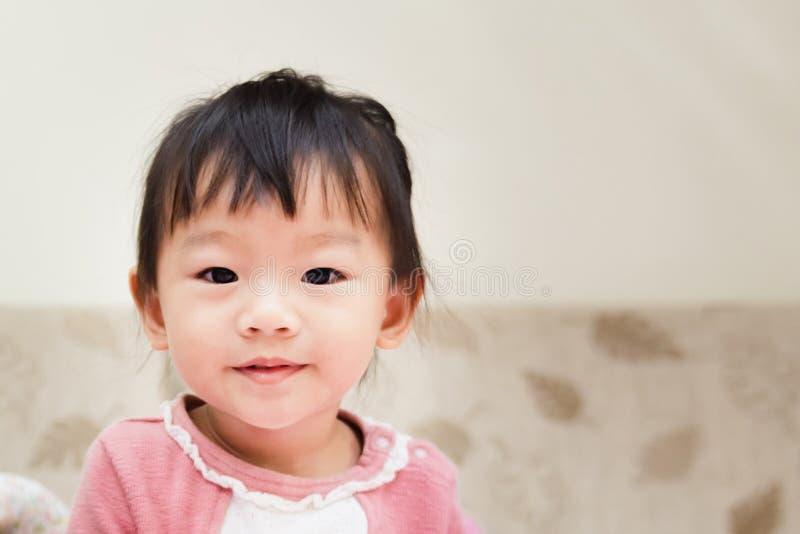 das glückliche kleine Kind, das nach lächelt, wachen auf und über dem Bett an einem entspannten Morgen, das spielt lizenzfreies stockfoto