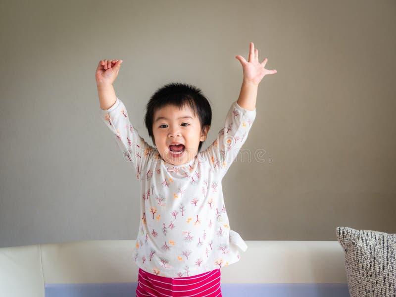 Das glückliche kleine nette lachende Mädchen und heben die Hand oben auf dem sof an stockfotos