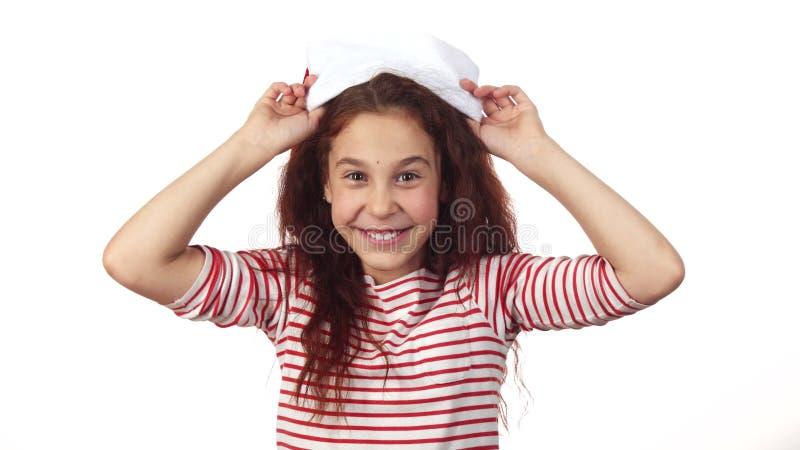 Das glückliche Mädchen, das auf einem Santa Claus-Hut versucht lizenzfreie stockfotos