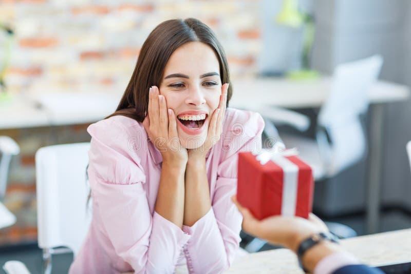 Das glückliche Mädchen, das im Büro arbeitet, empfing ein Geschenk lizenzfreies stockbild