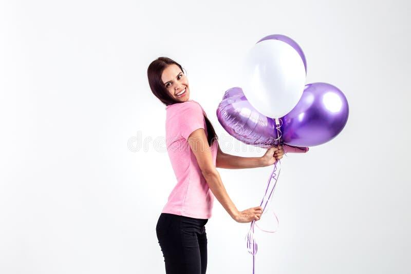 Das glückliche Mädchen, das im rosa T-Shirt und in den Jeans gekleidet wird, hält Ballone in ihren Händen auf dem weißen Hintergr stockfoto