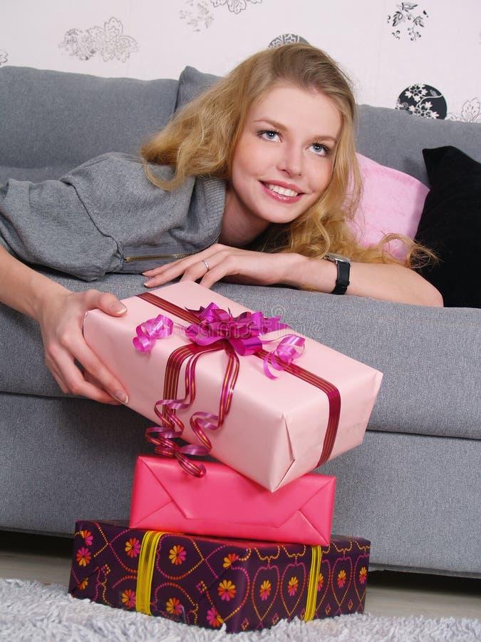 Das glückliche Mädchen liegt auf einem Sofa und betrachtet Geschenke lizenzfreies stockfoto