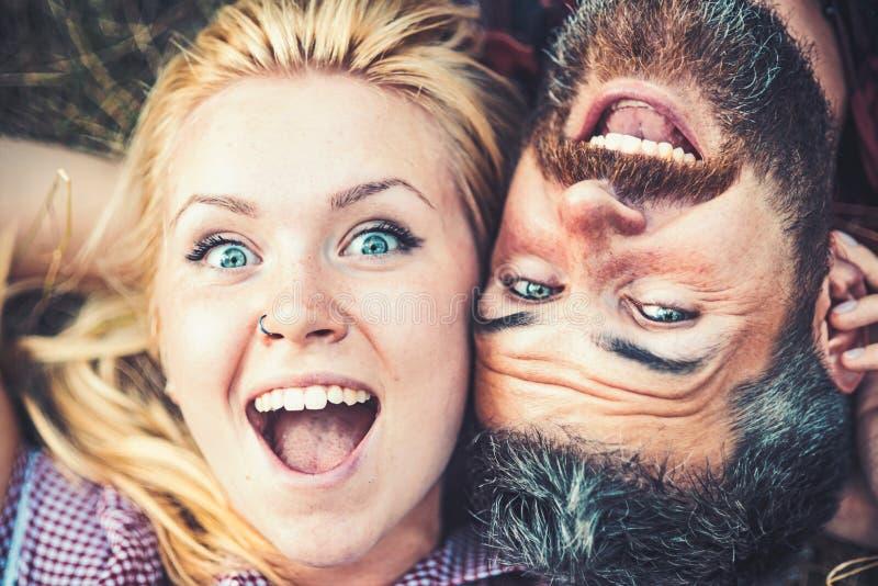 Das glückliche Paar, das auf Gras in den netten Knaben des Parks oder des Waldes in der Liebe sehen liegt nebeneinander, von oben lizenzfreie stockbilder