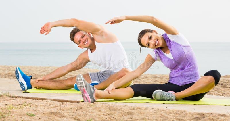 Das glückliche Paar, das Yoga tut, wirft das Sitzen auf sonnigem Strand auf stockfoto