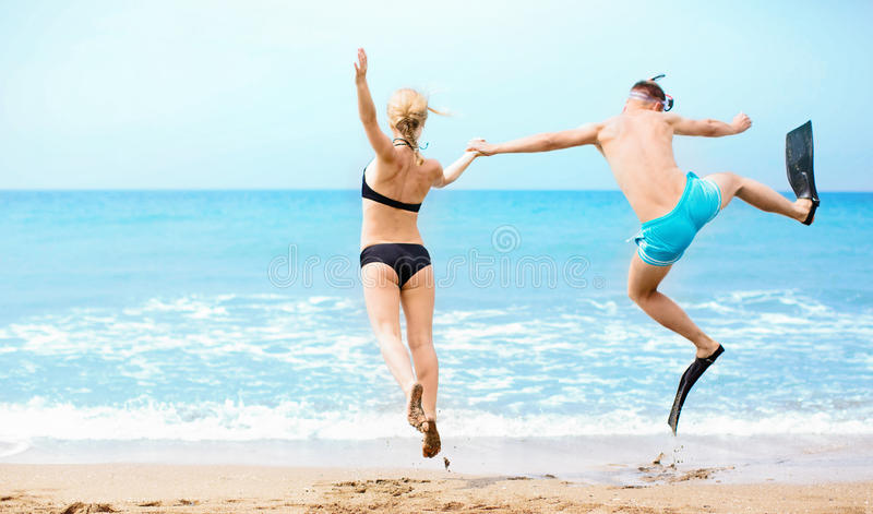 Das glückliche Paar springend in das Meer stockfotos