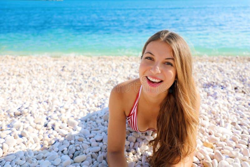 Das glückliche schöne lächelnde Mädchengenießen entspannen sich das Lügen auf dem Strand, der Kamera betrachtet Sexy weibliche Fa lizenzfreie stockfotos