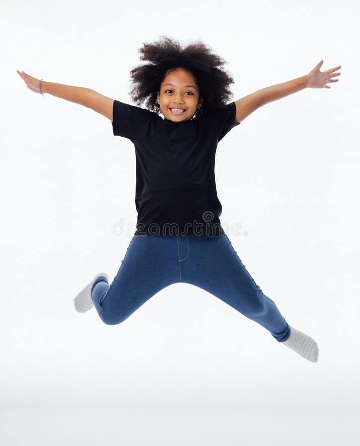 Das glückliches und Spaß Afroamerikanerschwarzkind, das mit den Händen springt, hob lokalisiert über weißem Hintergrund an stockbild