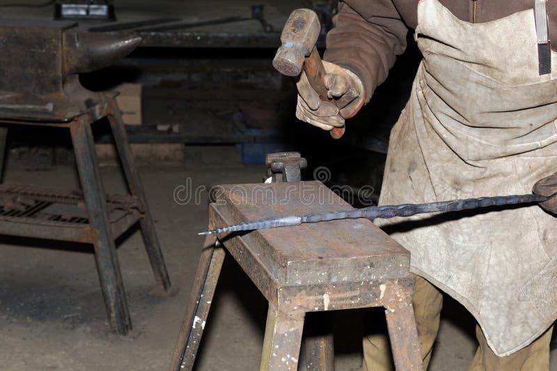 Das Glühen hämmern Stahl - zu Man muss das Eisen schmieden, solange es heiß ist stockfotografie