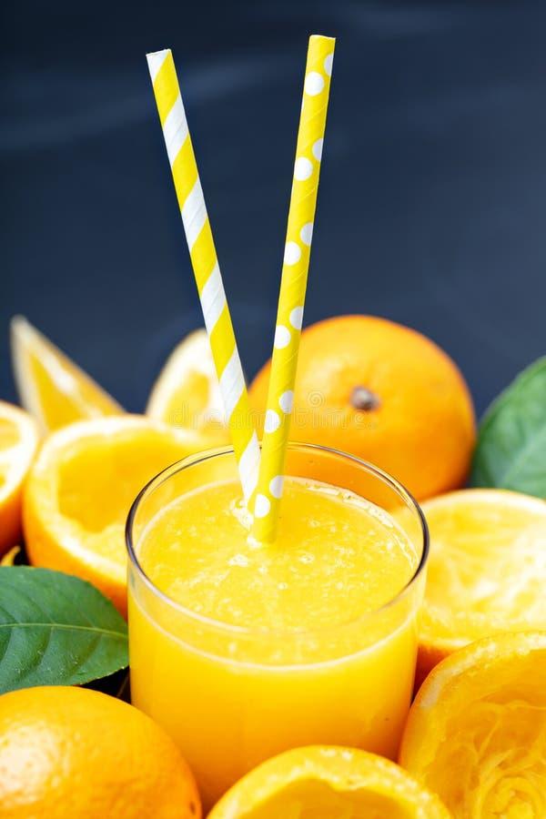 Das Glas Orangensaft umgeben durch Orange drückte Hälften und w zusammen stockfoto