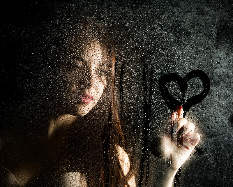 Das glatte Porträt des sexy Modells, aufwerfend hinter dem transparenten Glas, das durch Wassertropfen abgedeckt wird und zeichne stockbilder