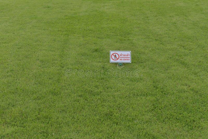Das Gras auf dem Feld und den Warnzeichen, die gehenden int verbieten lizenzfreie stockfotografie