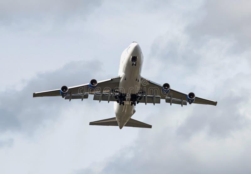 Das große schwere Jumbojet Fracht-Flugzeugfliegen, das mit blauem Himmel obenliegend ist, füllte mit Wolken lizenzfreie stockbilder
