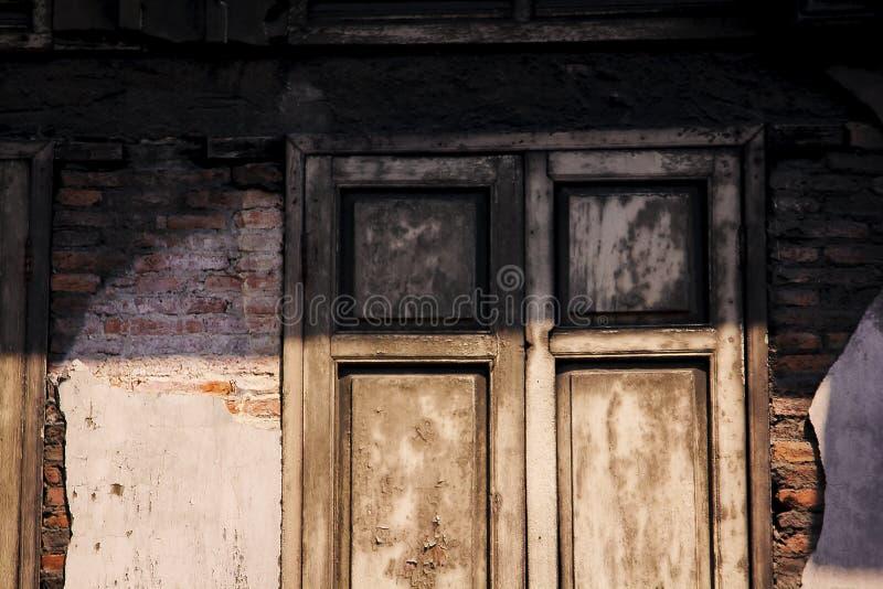 Das hölzerne Fenster ist auf einer alten Backsteinmauer stockbild