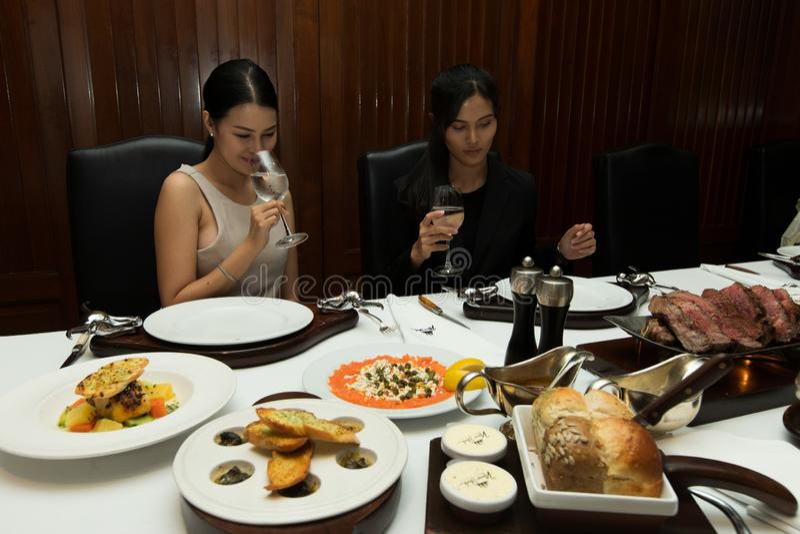 Das Haar mit zwei Frauen haben, zu Mittag zu essen großer Stück Steakgrill lizenzfreies stockbild