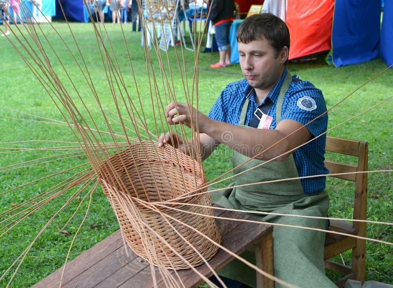 Das handicraftsman spinnt einen Korb von einer Stange an der Messe der nationalen Kreativität stockbild