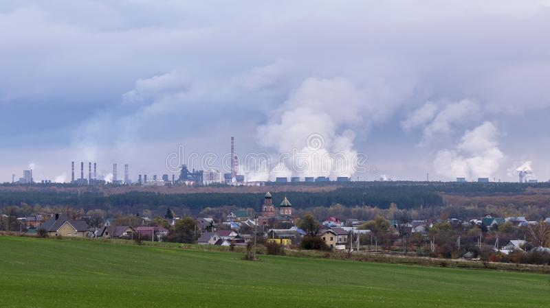 Das Haus auf dem Hintergrund von rauchenden Schloten der enormen Fabrik stockfotos
