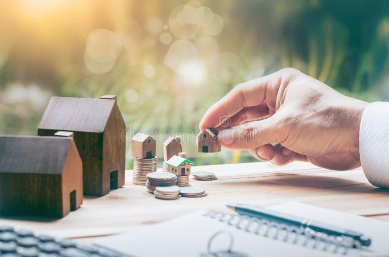 Das Haus, das auf Münzen Männer ` s Hand gesetzt wird, plant Einsparungensgeld von Münzen, um ein Haus zu kaufen lizenzfreie stockfotografie