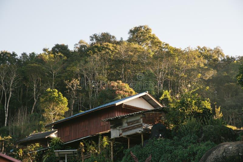 Das Haus des Dorfbewohners mit Bäumen und Berg im Hintergrund im Akha-Dorf von Maejantai auf dem Hügel in Chiang Mai, Thailand stockfoto
