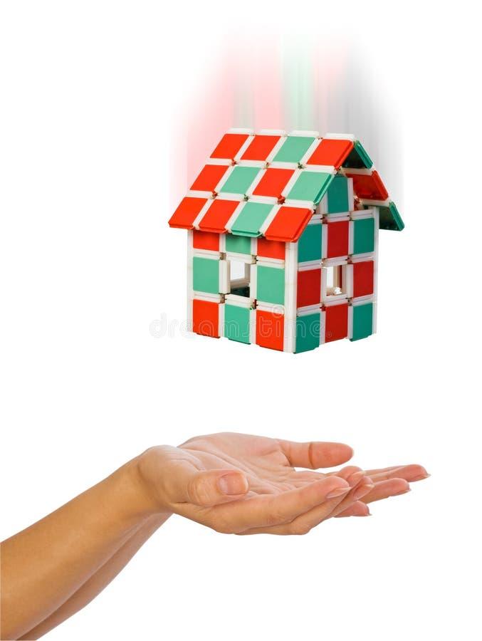 Das Haus fällt unten zu den menschlichen Händen stockfotografie