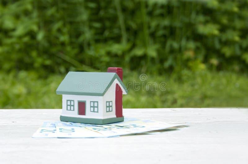 Das Haus ist auf den zwanzig Eurorechnungen Inneres gebildet von den Kirschtomaten Immobilien, Investition, Hypothek lizenzfreie stockbilder