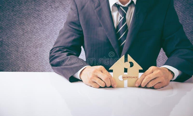 Das Haus und die Münzen werden auf ein Stück Puzzlespiele mit letztem Stück mit Texthypothek gesetzt stockbild