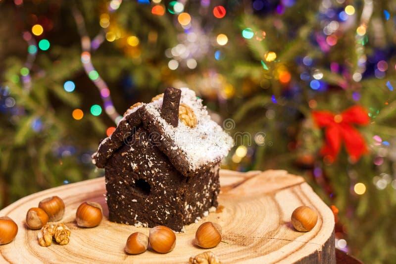 Das Haus, das von zerquetschten getrockneten Pflaumen, Nüsse gemacht wird, Daten steht auf rundem hölzernem Brett auf Weihnachtsb stockbilder