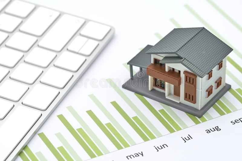 Das Hausmodell wird auf das Leistungsblatt gesetzt, das Balkendiagramm lizenzfreies stockbild