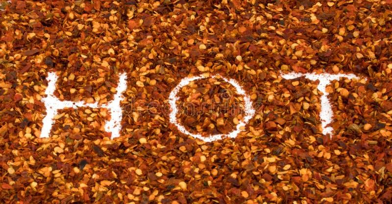 Das heiße Wort schreiben in getrocknetes lokalisiertes Makro des Pfeffers des roten Paprikas Zerstampfungen stockbilder