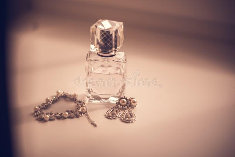 Das heiratendes gesetztes Parfüm der Braut, Ohrringe, Halskette, Juwelringe und Spitzestrumpfband auf Holztisch stockbilder