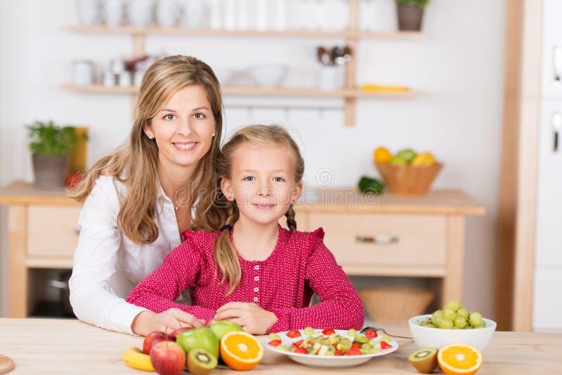 Das Helfen des recht kleinen Mädchens bereiten einen Obstsalat zu lizenzfreie stockbilder