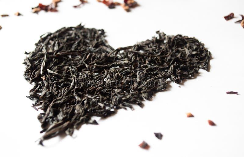 Das Herz der Teeblätter auf einem weißen Hintergrund lizenzfreies stockbild