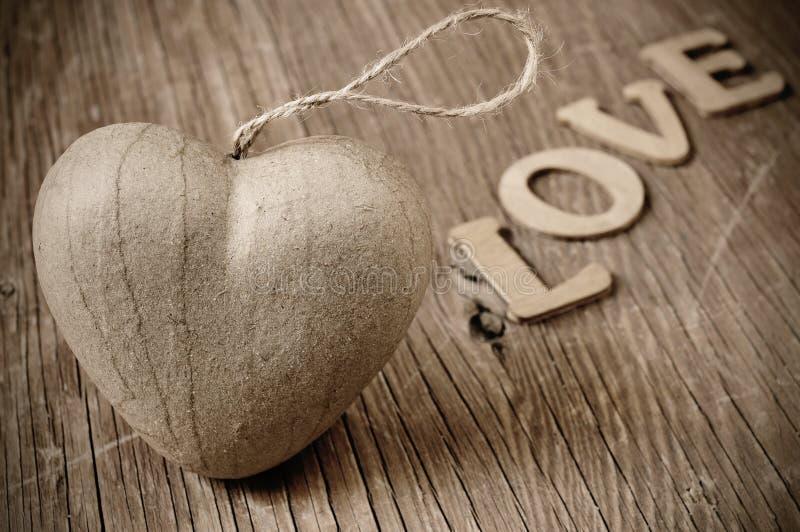Das Herz und Buchstaben, die das Wort bilden, lieben, beim Sepiatonen stockfoto