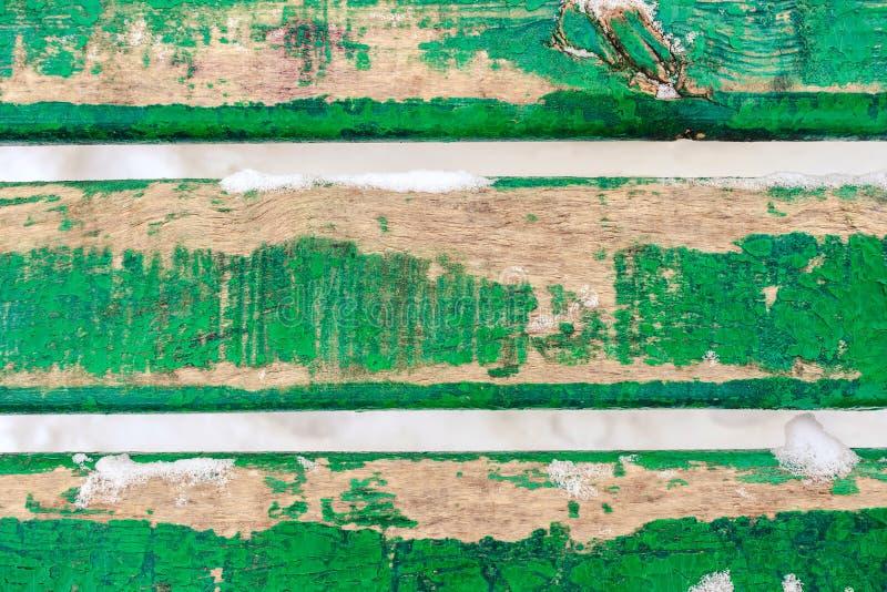 Das Hintergrundbild, das von drei alten grünen hölzernen Brettern gemacht wurde, bedeckte Schnee lizenzfreie stockbilder