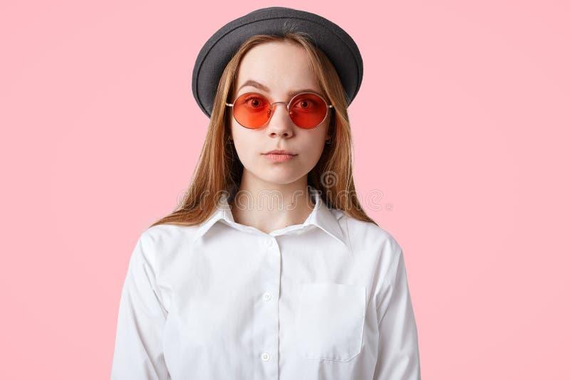 Das horizontale Porträt des angenehmen Schauens weiblich mit attraktivem Blick, hat ernsten Ausdruck, trägt stilvolle rote Sonnen lizenzfreie stockfotografie