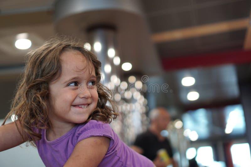 Das 4-jährige Mädchen lächelt in einem Fährenaufenthaltsraum stockfoto