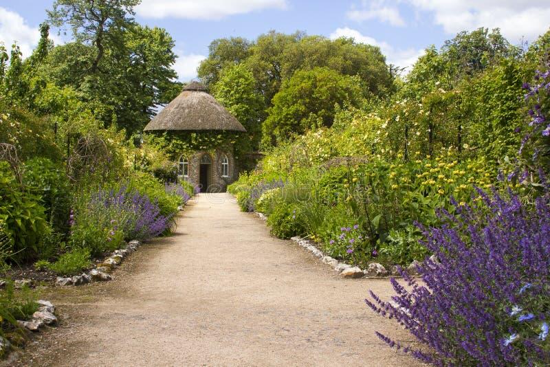 Das 19. Jahrhundert deckte ringsum das Haus mit Stroh durch schöne Blumenbeete und Kieswege im ummauerten Garten an Westdekan Gar lizenzfreie stockbilder
