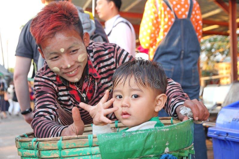 Das jugendlich Lächeln und ein kleiner Junge ist im Korb der Wolle und des sma lizenzfreie stockfotografie