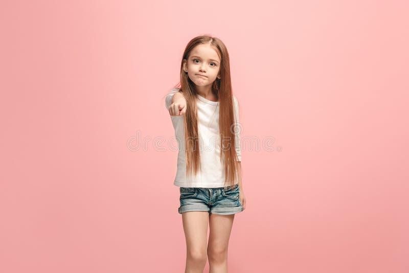 Das jugendlich Mädchen, das auf Sie, halbes Längennahaufnahmeporträt auf rosa Hintergrund zeigt lizenzfreie stockfotos