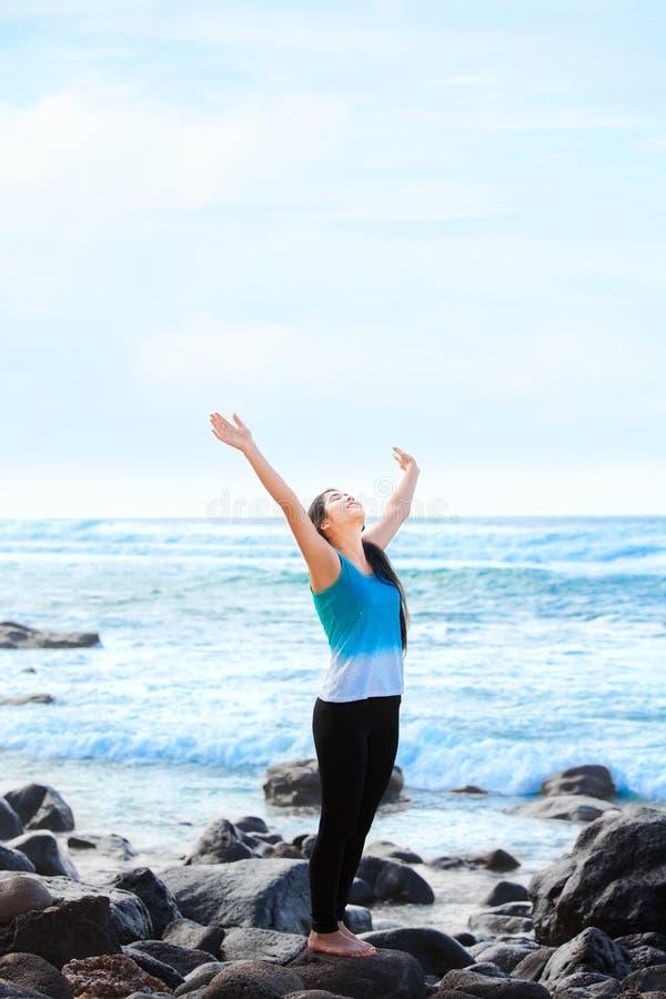 Das jugendlich Mädchen, das auf Armen des felsigen Strandes steht, hob an und pries Gott stockfotografie