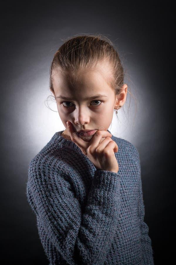 Das jugendlich Mädchen 9-12 Jahre alt, untersucht den Rahmen, emotionales Studioporträt auf einem grauen Hintergrund lizenzfreies stockbild