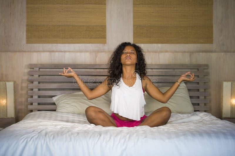 Das junge attraktive und glückliche schwarze hispanische Schlafzimmer der Frau zu Hause, das Yogameditation und Körperentspannung stockfotos