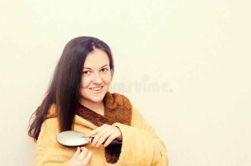 Das junge Brunettemädchen, das ihr Haar auf Weiß kämmt, lokalisierte Hintergrund Weibliches Porträt lizenzfreie stockbilder