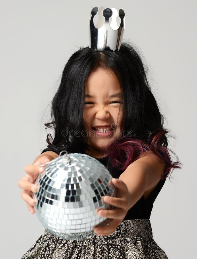 Das junge glückliche asiatische Mädchenkind, das in der silbernen Krone lächelt und geben weg Discoballdekoration stockfotografie